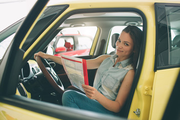 The young dark-haired woman examining car at the dealership and making his choice. Horizontal portrait of a young female model at the car. He is thinking if he should buy it
