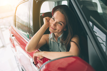 Closeup portrait happy, smiling, young attractive woman, buyer sitting in her new car isolated outside dealer, dealership lot office. Personal transportation, auto purchase concept