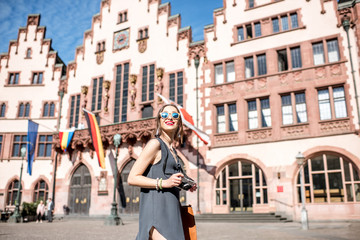 Young female tourist with photo camera enjoying visiting the old city center of Frankfurt city