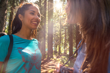 Woman smiling to friend at hiking trail path in forest woods during sunny day.Group of friends people summer adventure journey in mountain nature outdoors.Travel exploring Alps,Dolomites,Italy.