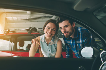 Happy couple chooses to buy a car in showroom. Beautiful young man and women in the auto show, choosing a car. Beautiful husband and wife standing at the car dealership and making their decision