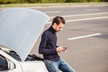 Man calling by phone to get help with his damaged car