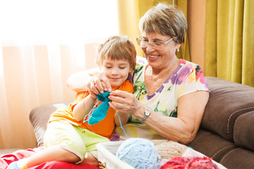 grandmother showing her grandson how to knit from yarn sitting on sofa in living room at home. the grandmother spends time together in with the grandson.