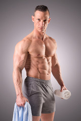 fit muscular man posing isolated on a grey background