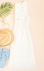 Summer fashion, summer outfit on cream background. White lace dress, blue flip flops and straw hat. Flat lay, top view