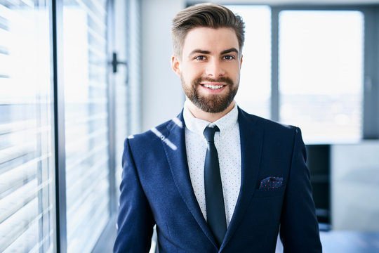 Young businessman looking straight at camera in his office