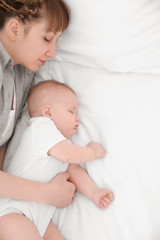 Young woman with cute baby sleeping on bed at home