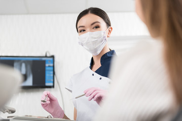Cheerful stomatologist preparing instruments for treatment teeth