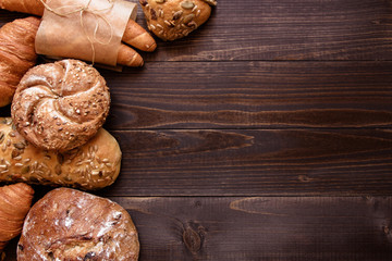 Fresh bread on the dark wooden background top view