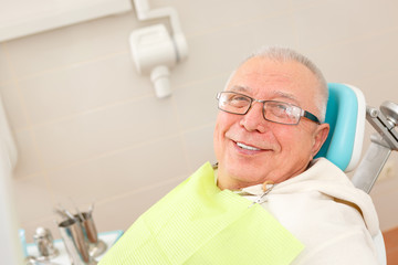 Old senior man with glasses sitting in a dental chair in a dentist's office.