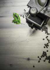telling story from the past - grinding roasted beans of coffee with old vintage retro grinder with ground coffee and green leaf in black and white top view on wooden background with copy space