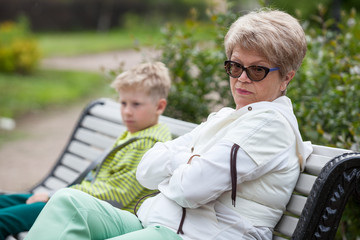 European grandmother and grandson conflict, two people sitting in closed poses on bench in park