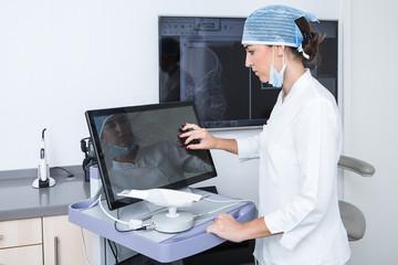 Female dentist working on desktop computer