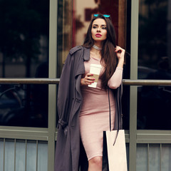 Young beautiful stylish woman with long straight brunette hair walking at the street. Pretty girl in pink elegant dress and coat holding shopping bag and cup of coffee.