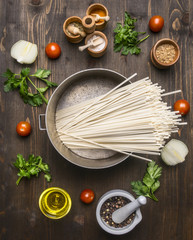 Cooking vegetarian noodles with cherry tomatoes, herbs and spices and oil on a wooden background, noodles lies in a vintage pot top view