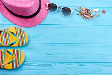 Beach accessories and sea shells. Female hat, slippers, glasses, sea shells. Summer dream of vacation.