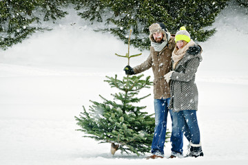 Heterosexual couple stands with Christmas tree in snow-covered landscape, Bavaria, Germany