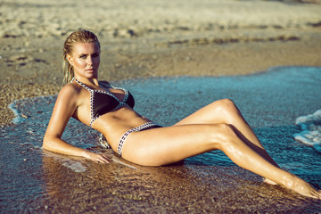 Beautiful suntanned glam blond woman with wet skin and hair lying on the beach and enjoying, her long legs washed by the sea waves. Resort and spa concept. Copy-space. Outdoor shot