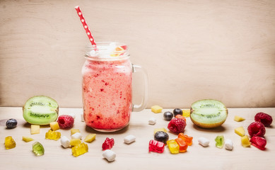 fresh fruit smoothies with berries, marshmallows, kiwi and jelly in bank with a pen on a white background wooden  close up