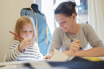 Caucasian woman working while her daughter drawing picture near her
