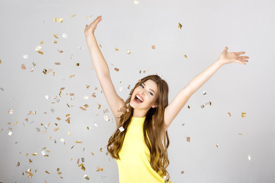 Beautiful happy brunette woman with long hair smiling and confetti falls everywhere. party time