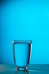 Glass on empty blue background