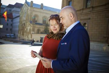 Senior couple looking at city map, Munich, Bavaria, Germany