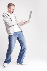 Youth Lifestyle Concepts and Ideas. Portrait of Happy Caucasian Man in Casual Clothing Posing with Laptop on Hands Against White Background.