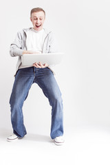 Youth Lifestyle Concepts and Ideas. Full Length Portrait of Happy Caucasian Man in Casual Clothing Posing with Laptop on Hands Against White Background.