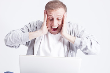Portrait of Extremely Surprised Caucasian Man with Laptop While Chatting. Posing Against White Background.Horizontal Image Composition