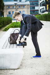 Young businessman putting on shoes, Munich, Bavaria, Germany
