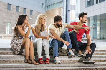 Group of students sitting on steps of college campus