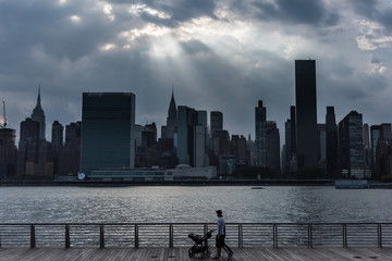 A silhouette of a couple walking on the waterfront in Long Island City.