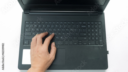 Wall mural hand on keyboard typing with notebook top view