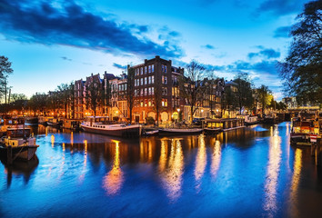 The most famous canals and embankments of Amsterdam city at night. General view of the cityscape and traditional Netherlands architecture.