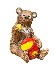A statuette of a bear cub that eats honey its paw