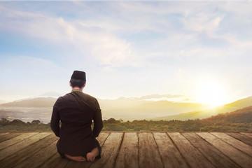 Portrait of muslim man kneeling and praying to god