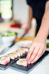 Hand of Chef preparing sushi in the kitchen