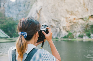 Back of professional travel photographer with camera while shooting landscape..Young woman taking photo of mountain..woman photographer taking photo at the lake.