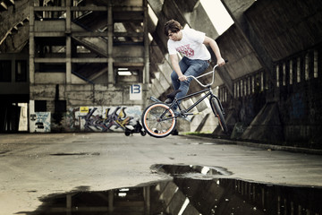 BMX biker performing a stunt over a puddle