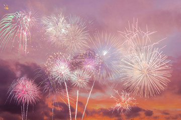 Beautiful colorful holiday fireworks in the sunset/evening sky with majestic clouds, long exposure. Concept of American Independence celebration. Happy Independence Day or Fourth of July banner.