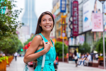 Wall Mural - Chinese woman shopping on Nanjing Road Shanghai city, China. Happy girl walking one of the world's busiest pedestrian street. Asian woman tourist visiting stores. Famous chinese attraction landmark.