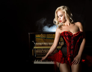 f1a52857e Young beautiful girl in red corset standing near the piano. Vintage style  beautiful woman.