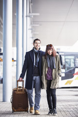 Happy young couple with luggage walking outdoors