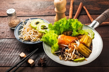 Chicken noodle with spice, herb and chopsticks on wood background