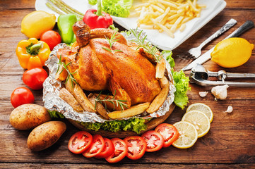 Whole roasted chicken with vegetables on wood table