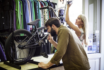 Young couple in bicycle shop looking at bike