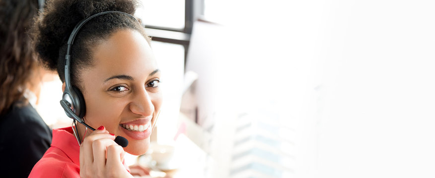 Smiling black businesswoman working in call center