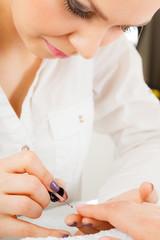 Woman in beauty salon getting manicure done.