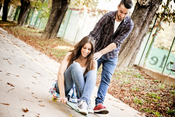 Young woman skateboarding, man supporting her